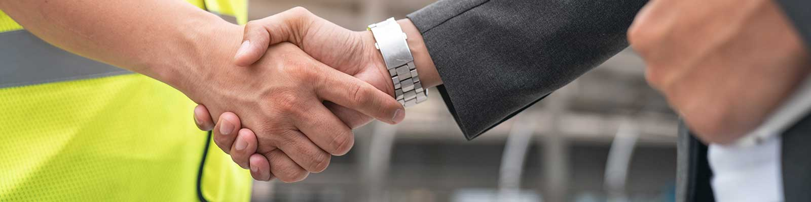close up of handshake between man in suit and construction vest