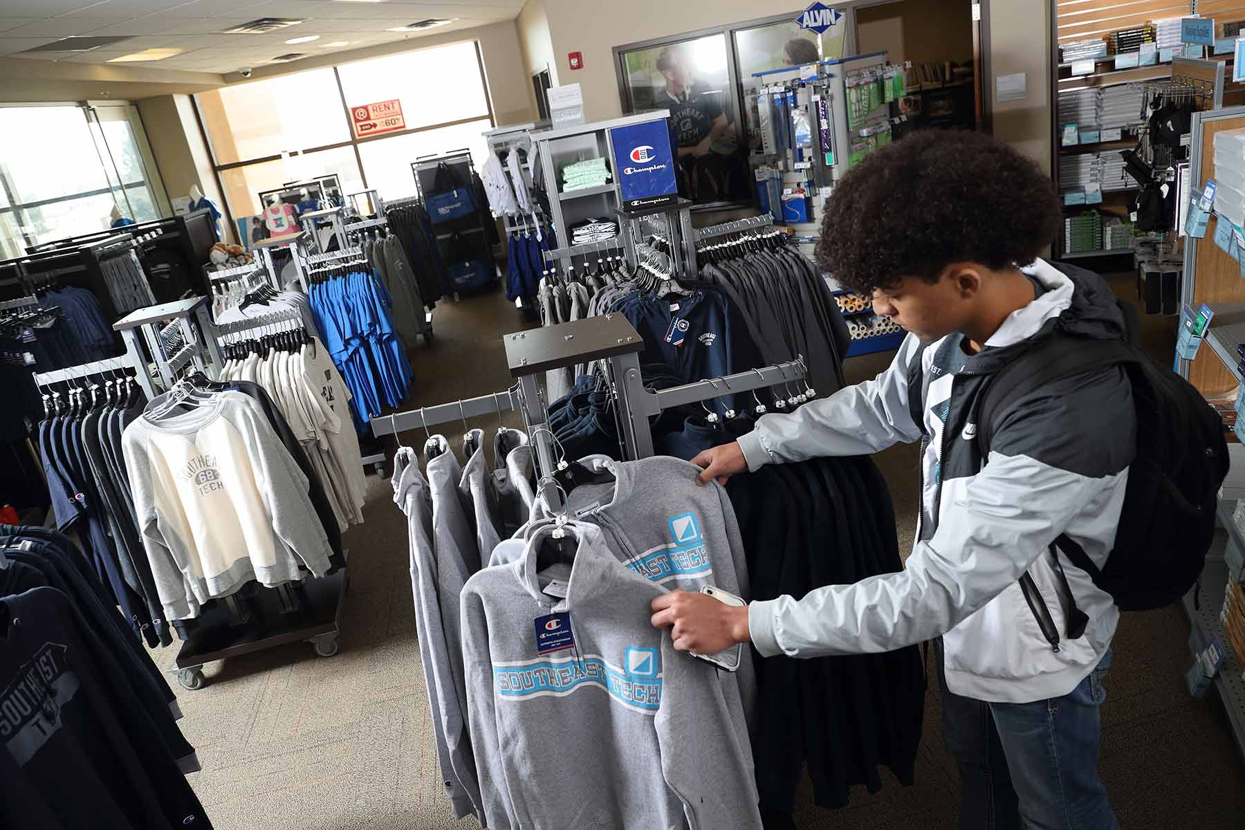 student looking at sweatshirts in a rack